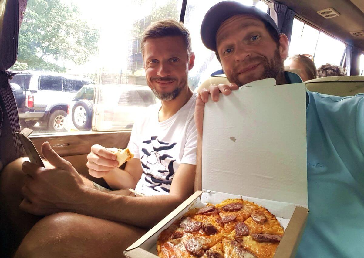 Tjalf Hoyer und Nicolas Scheidtweiler mit Pizza im Impala von Arusha nach Nairobi - 7summits4help für die German Doctors unterwegs