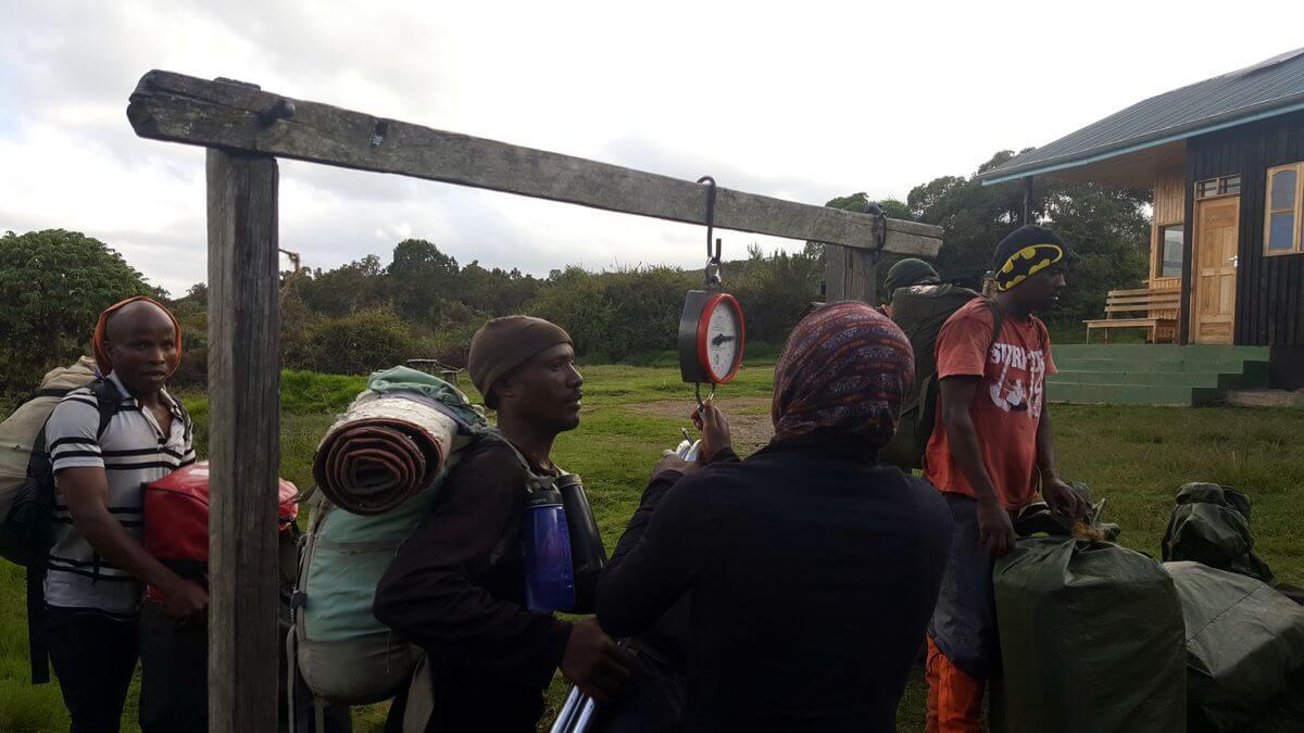 Träger wiegen ihre Last am Simba-Camp