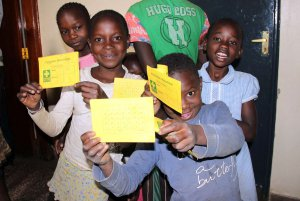 Kinder warten mit der Essenskarte an der Ausgabe